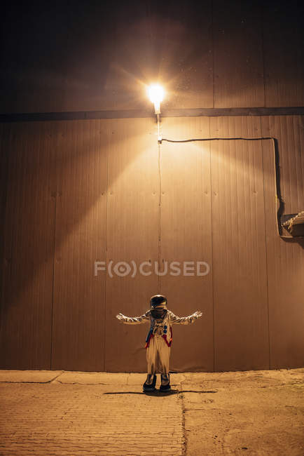 Spaceman standing under lamp at wall at night — Stock Photo