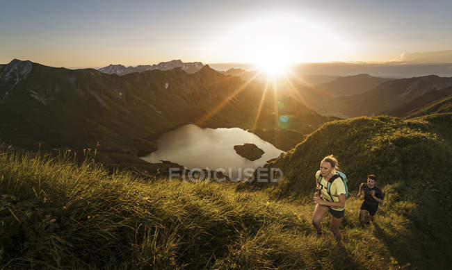 Germany, Allgaeu Alps, man and woman running on mountain trail — Stock Photo