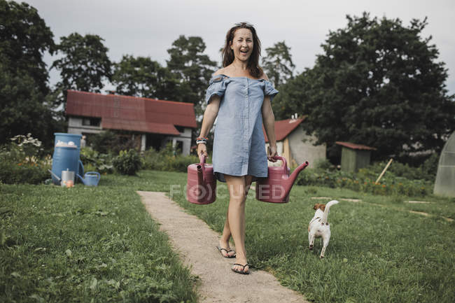 Happy woman with Jack Russel Terrier carrying watering cans in garden — Stock Photo