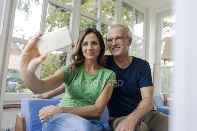 Усміхнена Зріла пара приймаючи селфі вдома — стокове фото