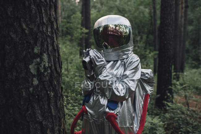 Spaceman exploring nature, filming trees in forest — Stock Photo