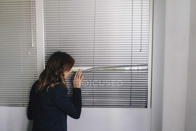 Женщина, стоящая у окна, шпионит через жалюзи — стоковое фото