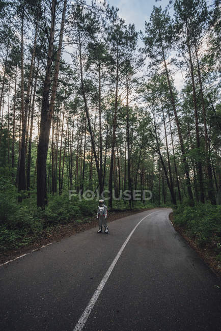 Spaceman que explora a natureza, estando na estrada na floresta — Fotografia de Stock