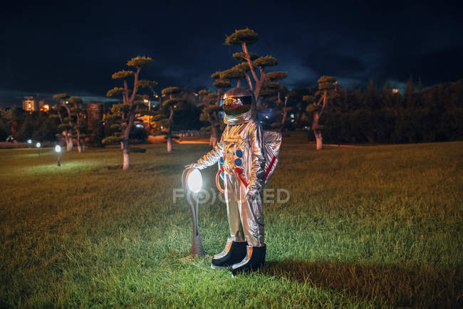 Spaceman standing at a lamp in park at night — Stock Photo
