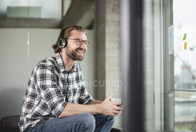 Счастливый случайный бизнесмен с чашкой кофе и гарнитурой в офисе — стоковое фото
