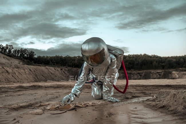 Spaceman que explora o planeta sem nome, pesquisando o solo — Fotografia de Stock