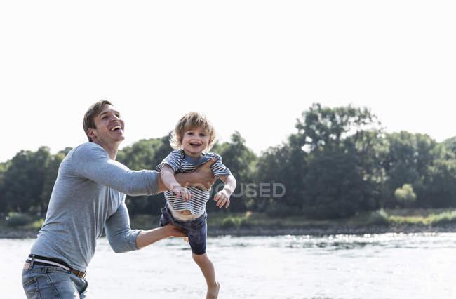 Père et fils gai ayant l'amusement au bord de la rivière — Photo de stock