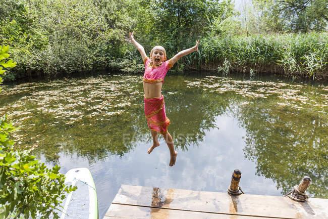 Menina despreocupada pulando em lagoa — Fotografia de Stock