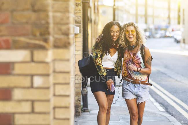 Felizes amigas caminhando e rindo na cidade — Fotografia de Stock