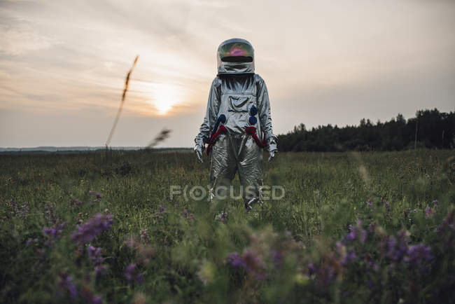 Spaceman exploring nature, standing in blooming meadow at sunset — Stock Photo