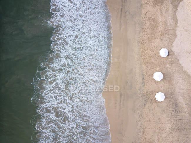 Indonésia, Bali, vista aérea da praia de Jimbaran, guarda-sóis brancos de acima — Fotografia de Stock