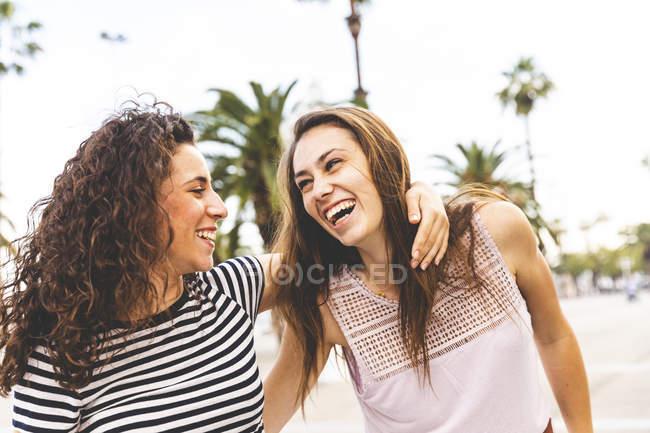 Duas amigas felizes no passeio com as palmas das mãos — Fotografia de Stock