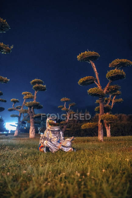 Spaceman in yoga pose siting in park at night — Stock Photo