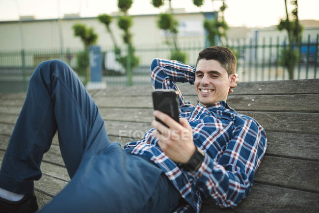 Young man lying and texting with smartphone outdoors — Stock Photo