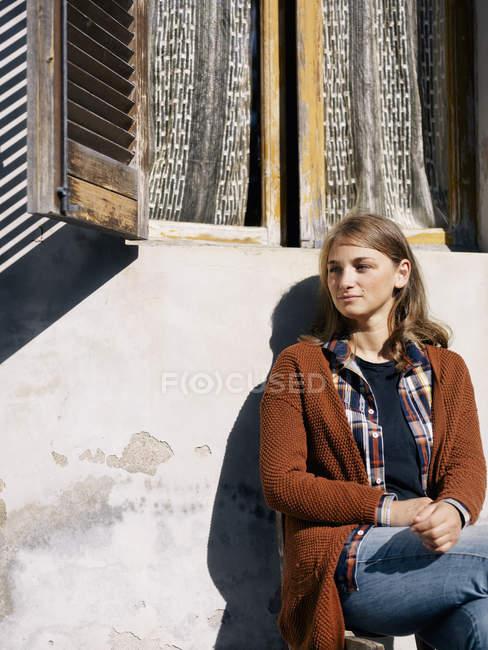 Портрет женщины, сидящей перед домом в сельской местности — стоковое фото