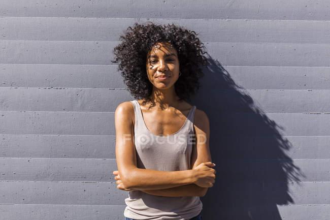 Retrato de mujer joven con el pelo rizado contra la pared - foto de stock