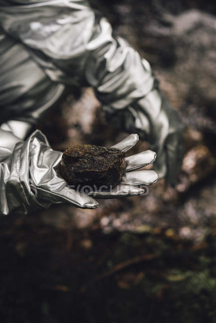 Close-up of spaceman exploring nature, holding soil — Stock Photo