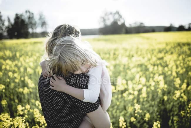 Портрет маленькой девочки на руках матери в поле изнасилования — стоковое фото