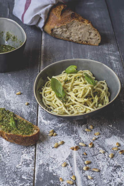 Homemade basil pesto, spaghetti in a bowl, rye baguette on wood — Stock Photo