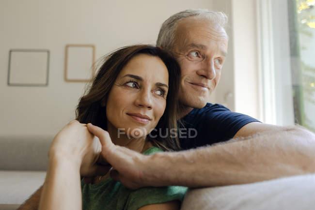 Sonriendo pareja madura sentada en el sofá en casa - foto de stock