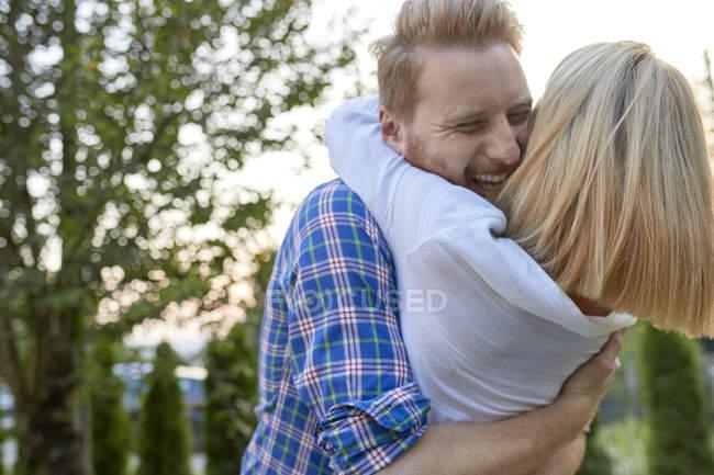 Счастливая пара обнимается на улице — стоковое фото
