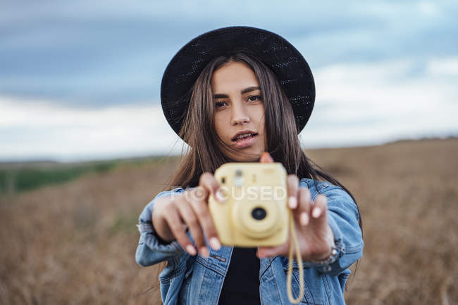Portrait of young woman taking photo of viewer — Stock Photo