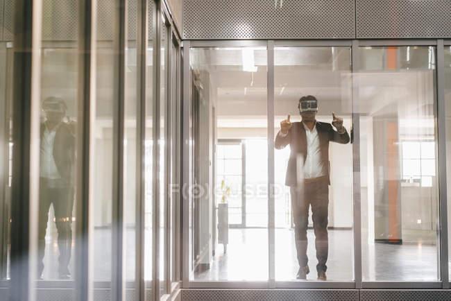 Бизнесмен, стоящий в офисном здании и смотрящий в очки виртуальной реальности — стоковое фото