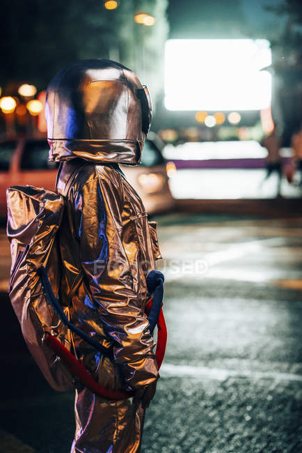 Spaceman on street in city at night attracted by shining projection screen — Stock Photo