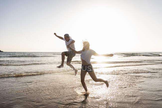 Молода пара веселяться на пляжі захід сонця, бризки води в морі — стокове фото