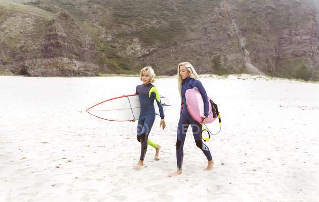 Spagna, Aviles, due giovani surfisti che camminano sulla spiaggia con tavole da surf — Foto stock