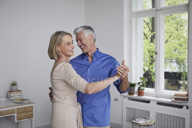 Feliz pareja madura bailando en casa - foto de stock