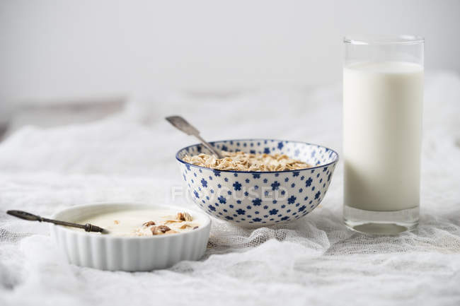 Bowls of granola, oat flakes and natural yoghurt and a glass of milk — Stock Photo