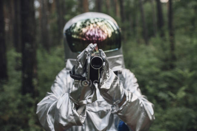 Spaceman exploring nature, filming trees — Stock Photo