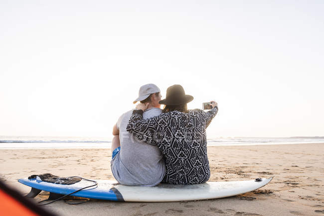 Couple camping on beach, taking smartphone selfie while sitting on surfboard — Stock Photo