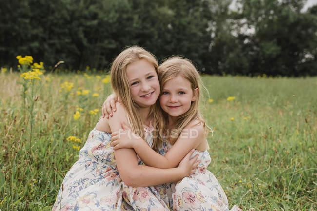 Дві молодші сестри обіймають одне одного на лузі. — стокове фото