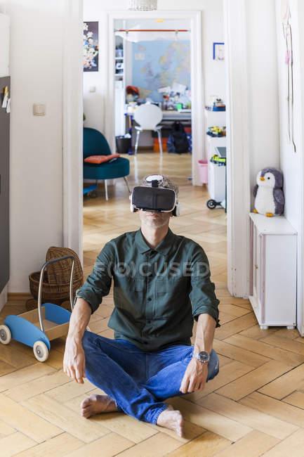 Зрелый мужчина сидит на полу дома, используя очки виртуальной реальности — стоковое фото