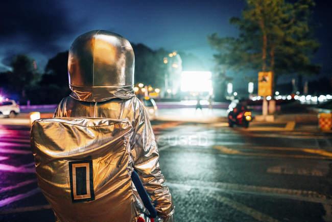 Космонавт, стоящий на площади ночью, привлекает сияющим проекционным экраном — стоковое фото