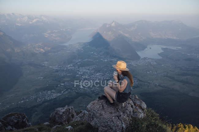 Suiza, Grosser Mythen, mujer joven en un viaje de senderismo sentada en una roca al amanecer bebiendo de la copa - foto de stock