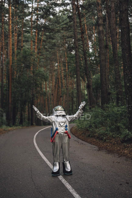 Spaceman standing with hands up on road in forest — Stock Photo