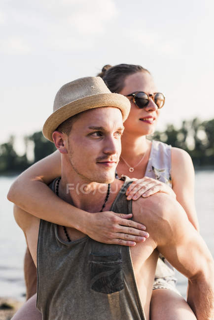 Young man giving girlfriend piggyback ride at riverbank — Stock Photo