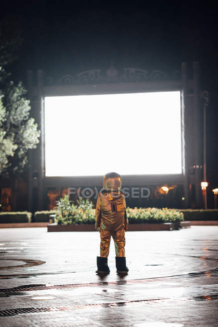 Raumfahrer steht nachts auf dem Platz, angelockt von leuchtender Projektionsfläche — Stockfoto