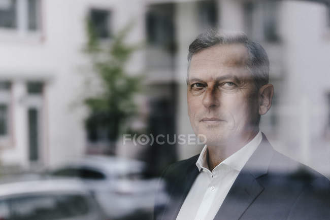Confident mature businessman looking out of window — Stock Photo