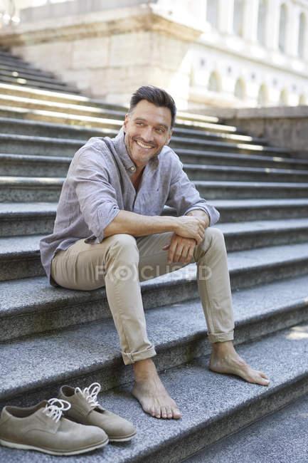Ritratto di uomo maturo sorridente seduto a piedi nudi sulle scale — Foto stock