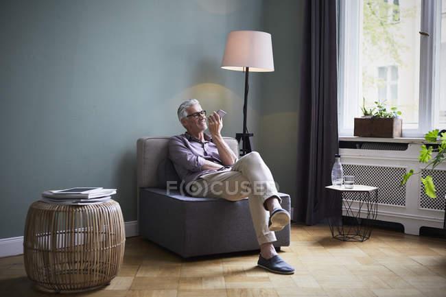 Homme mûr utilisant un téléphone portable à la maison — Photo de stock