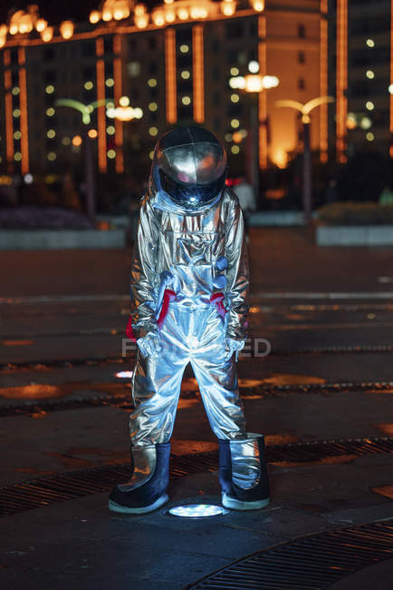 Spaceman standing at lamp on city square at night — Stock Photo
