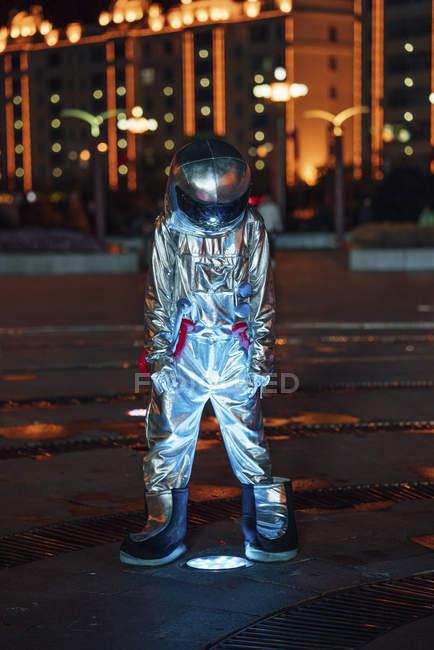 Космонавти стоять на ліхтарі на міській площі вночі — стокове фото