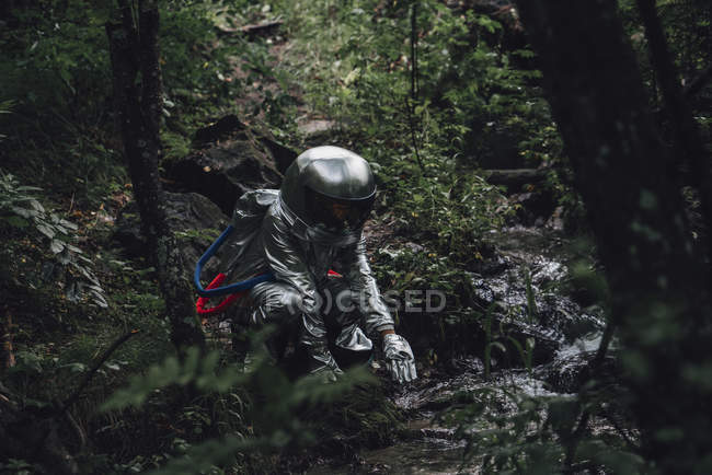 Spaceman exploring nature, crouching at brook in forest — Fotografia de Stock