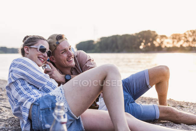 Young couple relaxing at the riverbank and sharing headphones — Stock Photo