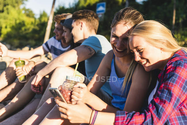 Gruppe fröhlicher Freunde, die draußen mit erfrischenden Getränken und Mobiltelefonen sitzen — Stockfoto