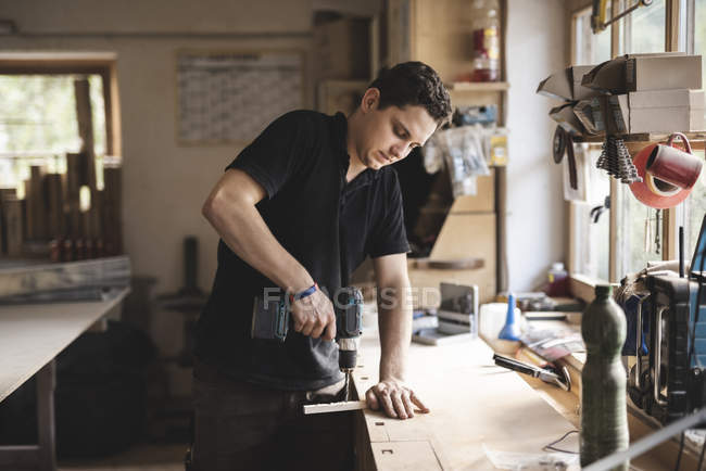Tischler mit Bohrer auf Holzstück in Werkstatt — Stockfoto